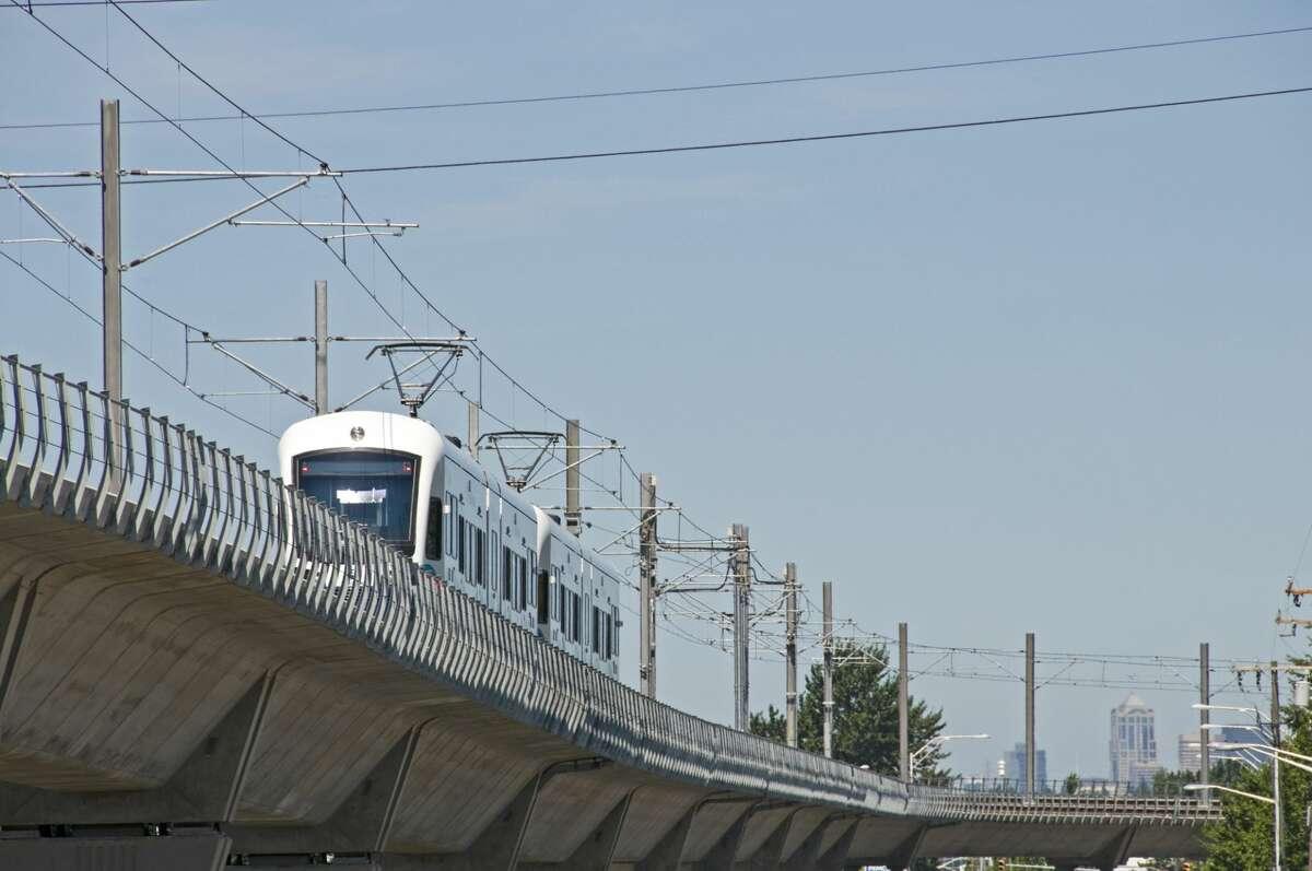Light rail train northbound on raised track.