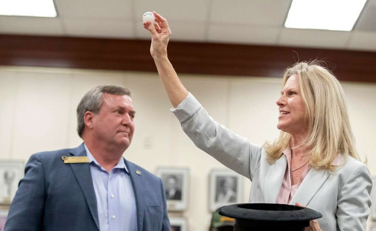 Mike Foreman, the mayor of Friendswood, and Julie Masters, the mayor of Dickinson, settle a runoff tie for mayor by pulling a Ping-Pong ball from a top hat.