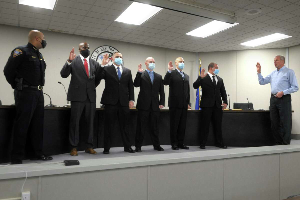 Police Chief Shawn Sequeira, left, looks on as Mayor Mark Lauretti, right, swears in new police officers, from left, Timothy Greene, John McMahon, Michael Dinihanian, Dominick Muoio and John Cannata at City Hall in Shelton, Conn. Jan. 11, 2021.