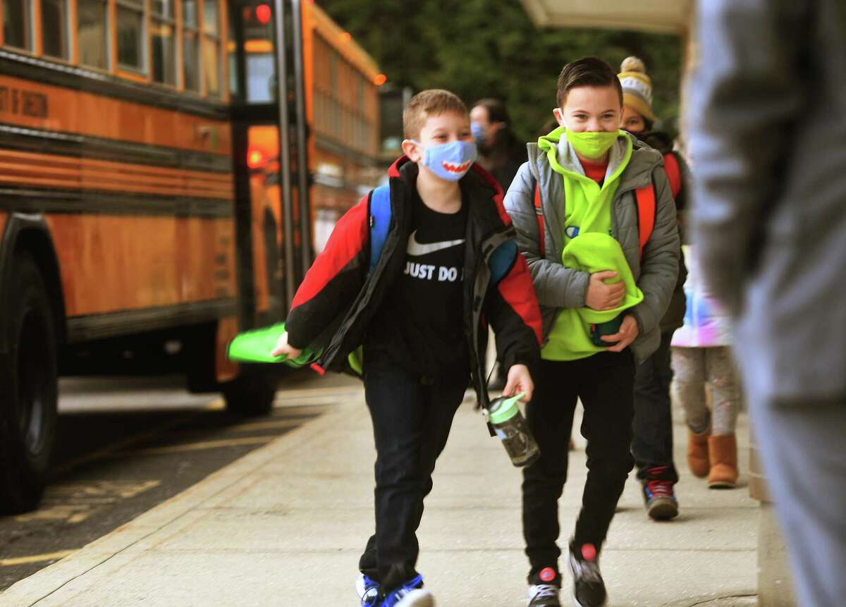 Students return to school after two months of remote home instruction at Long Hill Elementary School on Monday.