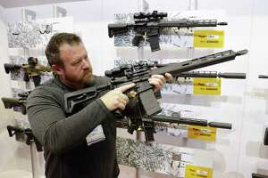 FILE - Bryan Oberc, Munster, Ind., tries out an AR-15 from Sig Sauer in the exhibition hall at the National Rifle Association Annual Meeting in Indianapolis, Saturday, April 27, 2019. Efforts to impose restrictions on firearms will soon have a supporter in the White House. But it's unlikely that big ticket items gun-control advocates have pined for will have much chance of passage given the tight margins in Congress and the increased polarization over gun issues. Much has changed in the past 12 years: more Americans own firearms and there are more AR-platform firearms in the civilian market. (AP Photo/Michael Conroy)