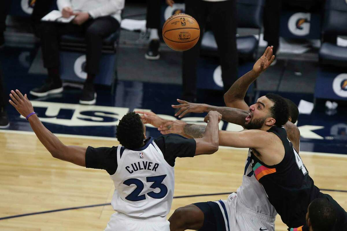 Spurs forward Trey Lyles goes for a rebound against the Timberwolves' Jarrett Culver, left, and Ed Davis in the second half on Sunday. In his first start of the season, Lyles grabbed 10 rebounds and played 35 minutes.