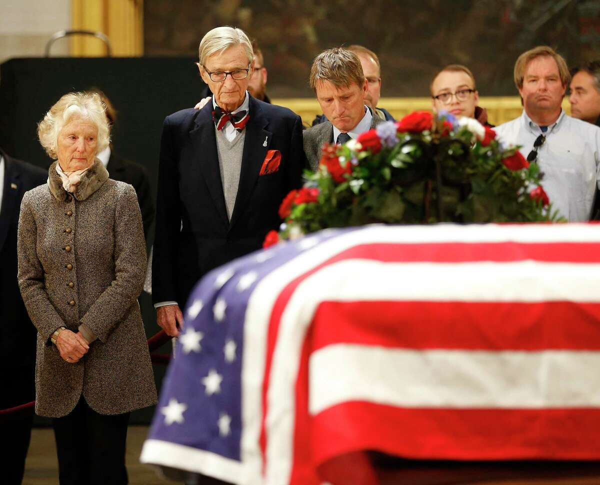 Jonathan Bush, brother of President George H.W. Bush and Nancy Walker Bush Ellis, his sister view his flad draped coffin as he laid in state at the United States Capitol Rotunda, Tuesday, Dec. 4, 2018, in Washington. Bush will lie in state in the Rotunda until Wednesday morning.