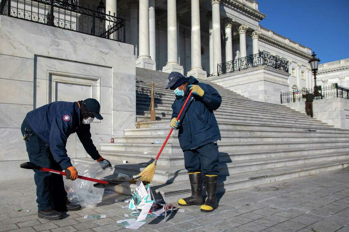 Yfrain Figueroa, left, and Raymond Andrew, both of whom work for Architect of the Capitol, clean up damage done to the U.S. Capitol.