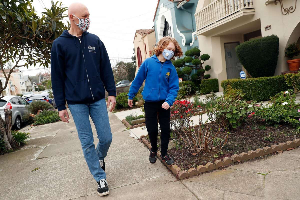 Bryan McDonald and his second grade son, Travis, walk home after being photographed at Dianne Feinstein Elementary School in San Francisco, Calif., on Sunday, January 10, 2021. McDonald objects to the school board's demand that the school change its name.
