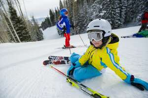 Young girl lying down on the slopes.