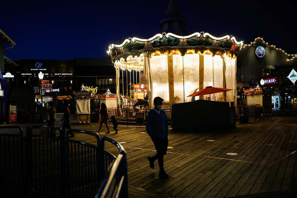Tourists pass by the carousel at Pier 39 at dusk on Wednesday, Nov. 25, 2020 in San Francisco, California. Despite a surge in COVID-19 cases hundreds of tourists came to visit Pier 39.