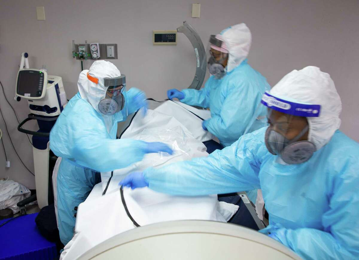 Lilly Castro, left, and and fellow registered nurses carefully place a dead patient into a body bag, inside the COVID-19 Intensive Care Unit at United Memorial Medical Center on Wednesday, Dec. 16, 2020, in Houston. The patient, who was intubated and went into cardiac arrest, died after six rounds of chest compressions and the efforts of nurses and doctors.