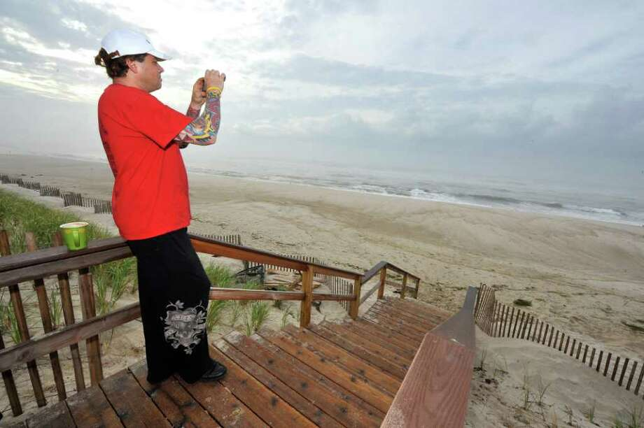Steve Cummings, of Quogue, photographs the Atlantic Ocean at Quogue Village Beach in Quogue, N.Y., as Hurricane Earl makes its way north along the Atlantic coastline on Friday, Sept. 3, 2010.  (AP Photo/Kathy Kmonicek) Photo: Kathy Kmonicek, AP / Associated Press