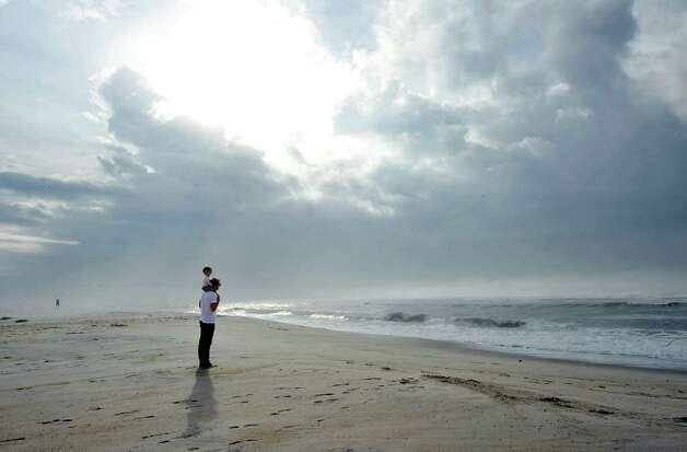 Michael Weber, of Brooklyn, N.Y., views the rough Atlantic Ocean surf from Hurricane Earl at Ponquogue Beach with his 1-year-old daughter Mikka on his shoulders early Friday, Sept. 3, 2010, in Hampton Bays, N.Y. (AP Photo/Kathy Kmonicek) Photo: Kathy Kmonicek, AP / Associated Press