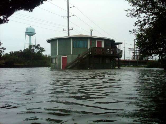 A home is seen in flood waters created by rain as Hurricane Earl swept through the area, in Buxton, N.C., Friday, Sept. 3, 2010. Hurricane Earl kicked up dangerous waves and rip currents along the East Coast as it blew over open water Friday toward Cape Cod after brushing North Carolina's Outer Banks, leaving flooding but no injuries on the narrow vacation islands.(AP Photo/Mike Baker) Photo: Mike Baker, ASSOCIATED PRESS / AP