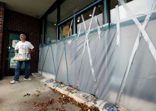 R.V. Hodge removes sandbags from a storefront  in Beaufort, N.C., as residents return to business as usual after Hurricane Earl brushed past the North Carolina coast Friday, Sept. 3, 2010. (AP Photo/Chuck Burton) Photo: Chuck Burton, ASSOCIATED PRESS / Associated Press