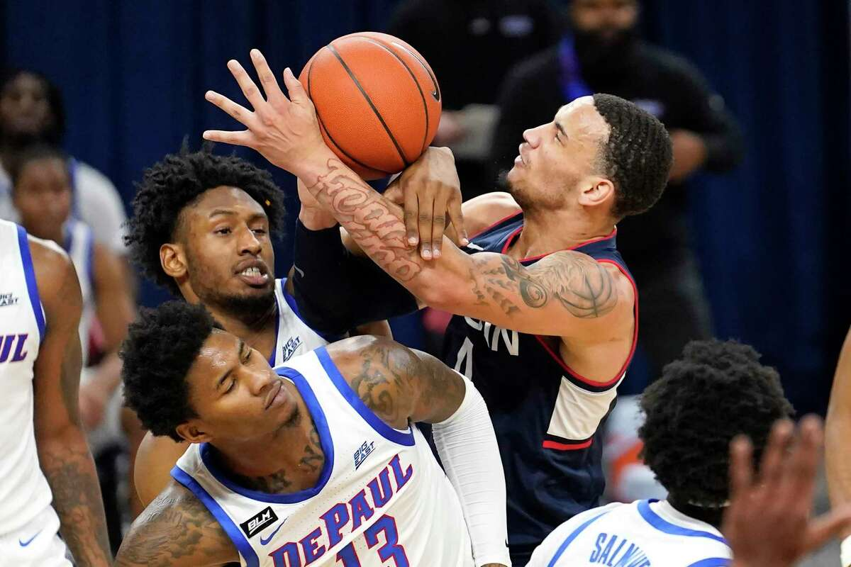 Connecticut's Tyrese Martin, right, battles DePaul's Pauly Paulicap and Darious Hall (13) for the ball during the first half of an NCAA college basketball game Monday, Jan. 11, 2021, in Chicago. (AP Photo/Charles Rex Arbogast)