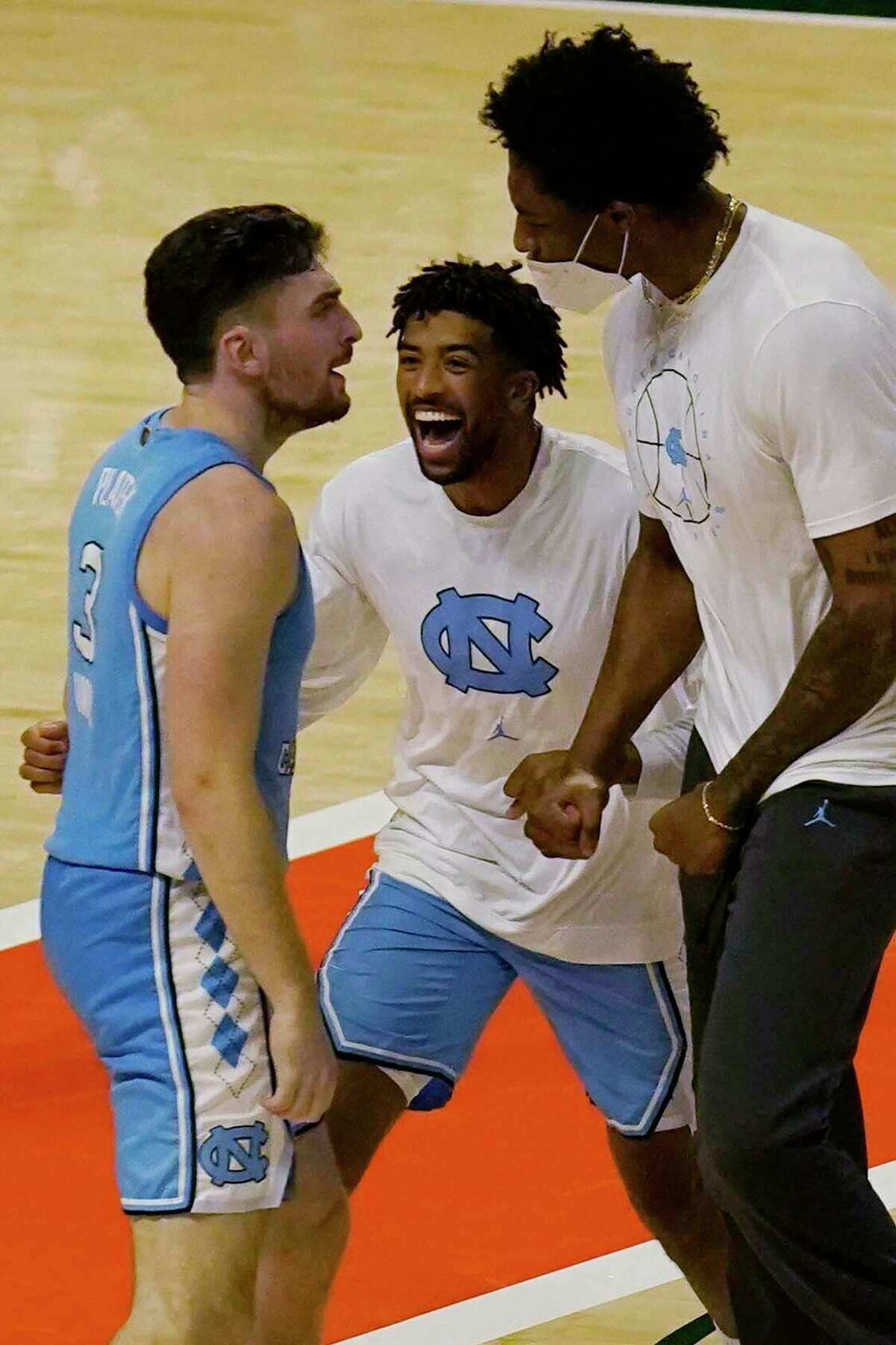Teammates congratulate guard Andrew Platek (3) after he scored the winning basket during the second half of an NCAA college basketball game against Miami, Tuesday, Jan. 5, 2021, in Coral Gables, Fla. North Carolina defeated Miami 67-65.