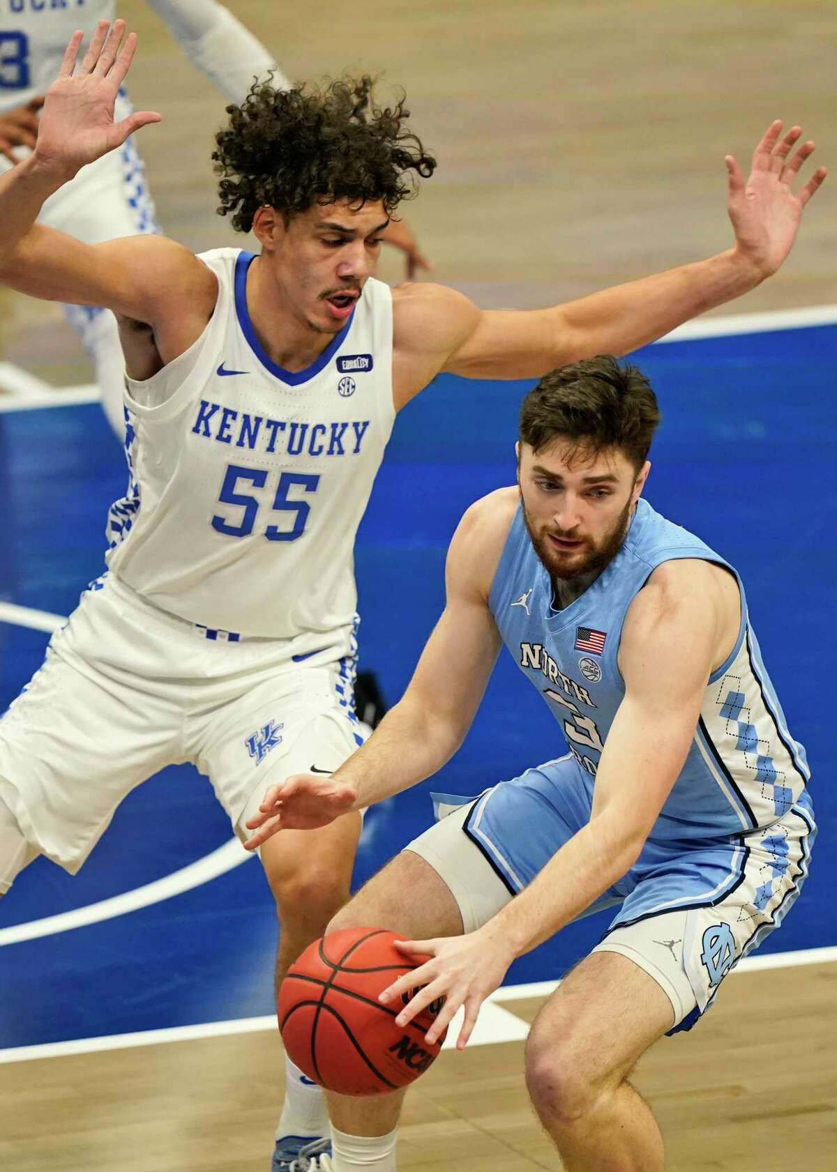 North Carolina's Andrew Platek (3) drives against Kentucky's Lance Ware (55) in the first half of an NCAA college basketball game, Saturday, Dec. 19, 2020, in Cleveland.