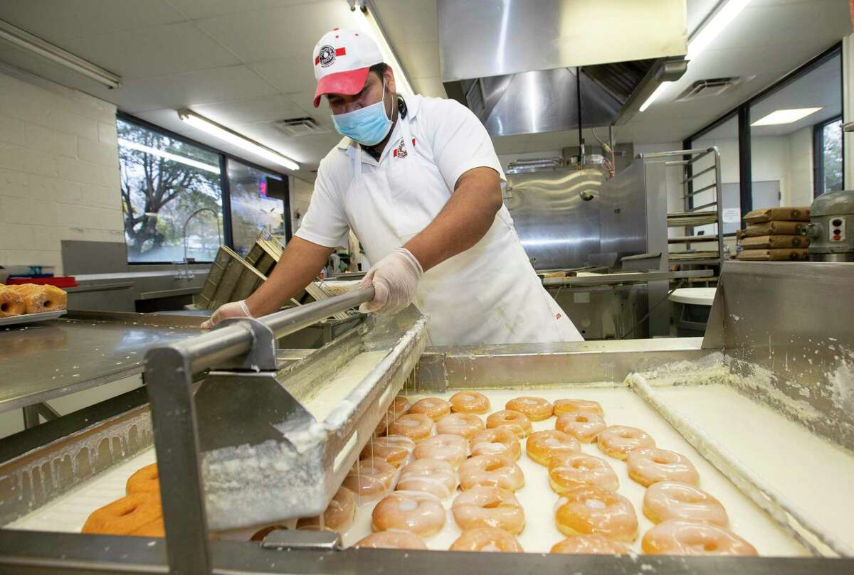 Shipley's Do-Nuts Baker Antonio Hernandez pours glaze over a batch of doughnuts Monday, Jan. 11, 2021, in Houston. The Paycheck Protection Program is rolling out its second round. In it, small business owners such as Alan Bergeron, who owns two Shipley's franchises, will be able to apply for a second loan starting Wednesday.