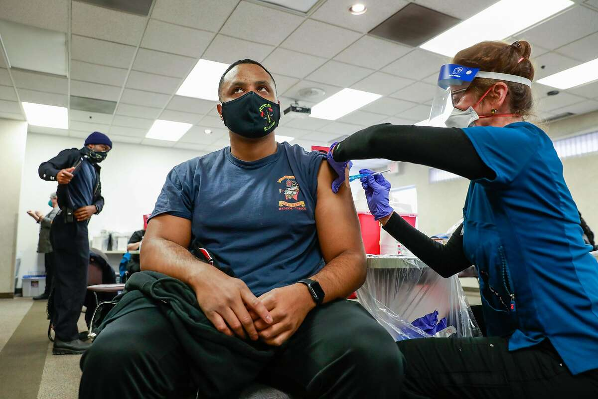 Mario Jones (left), with the Oakland Fire Department, gets his second dosage of the Pfizer vaccine from nurse Virginia Barrett (right) at St. Rose Hospital on Wednesday, Jan. 6, 2021 in Hayward, California. They were administering both the first dosage and second dosage of the vaccine.