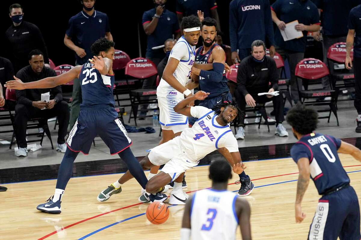 DePaul's Javon Freeman-Liberty (4) loses control of the ball as Connecticut's Josh Carlton (25) defends during the first half of an NCAA college basketball game Monday, Jan. 11, 2021, in Chicago. (AP Photo/Charles Rex Arbogast)