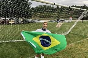 Rotary exchange student Alan Vilela of Brazil, 18, holds up the flag of Brazil while wearing his Dow soccer uniform. (Photo provided/Matt Rassette)