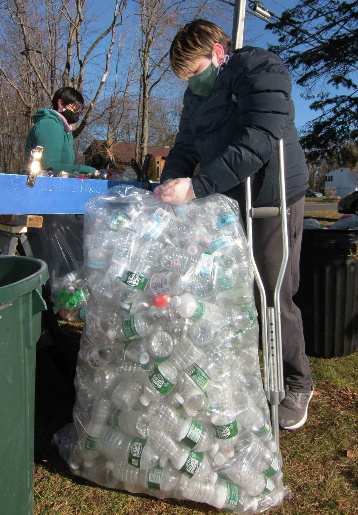 Scout Tim Andrade, 12, ties a full bag of plastic bottles during Boy Scout Troop 25's monthly redeemable bottle and can drive at First United Methodist Church in Shelton, Conn., on Saturday Jan. 9, 2021. The event, which helps raise money for scouting activities, is held each first Saturday of each month from 10 a.m. to 1 p.m.