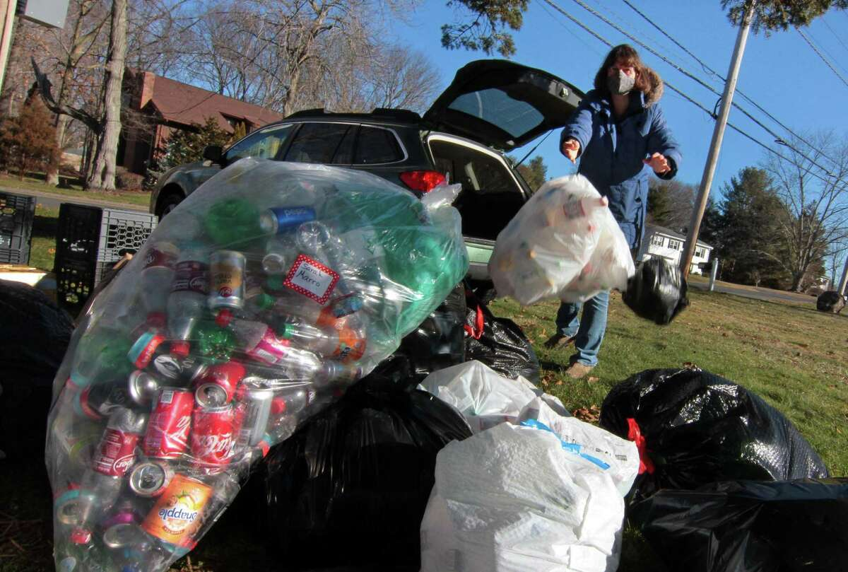 Scout mom Maggie Andrade tosses donated cans and bottles into the growing pile.