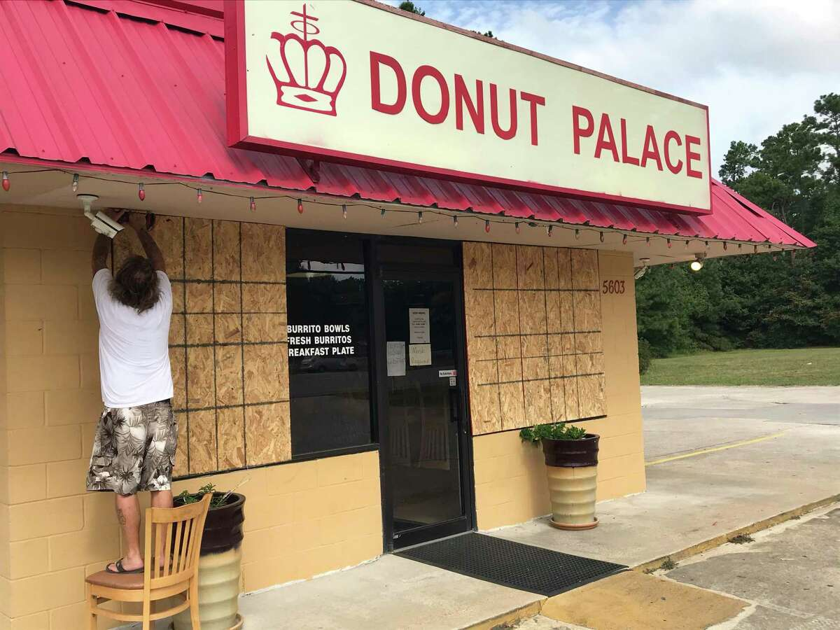 Fred Collins, 61, screws plywood to cover windows on the Donut Palace along Texas 87 north of downtown Orange, Texas, on Aug. 25, 2020. Orange County officials ordered a mandatory evacuation as Hurricane Laura threatens the northern Texas Gulf Coast.