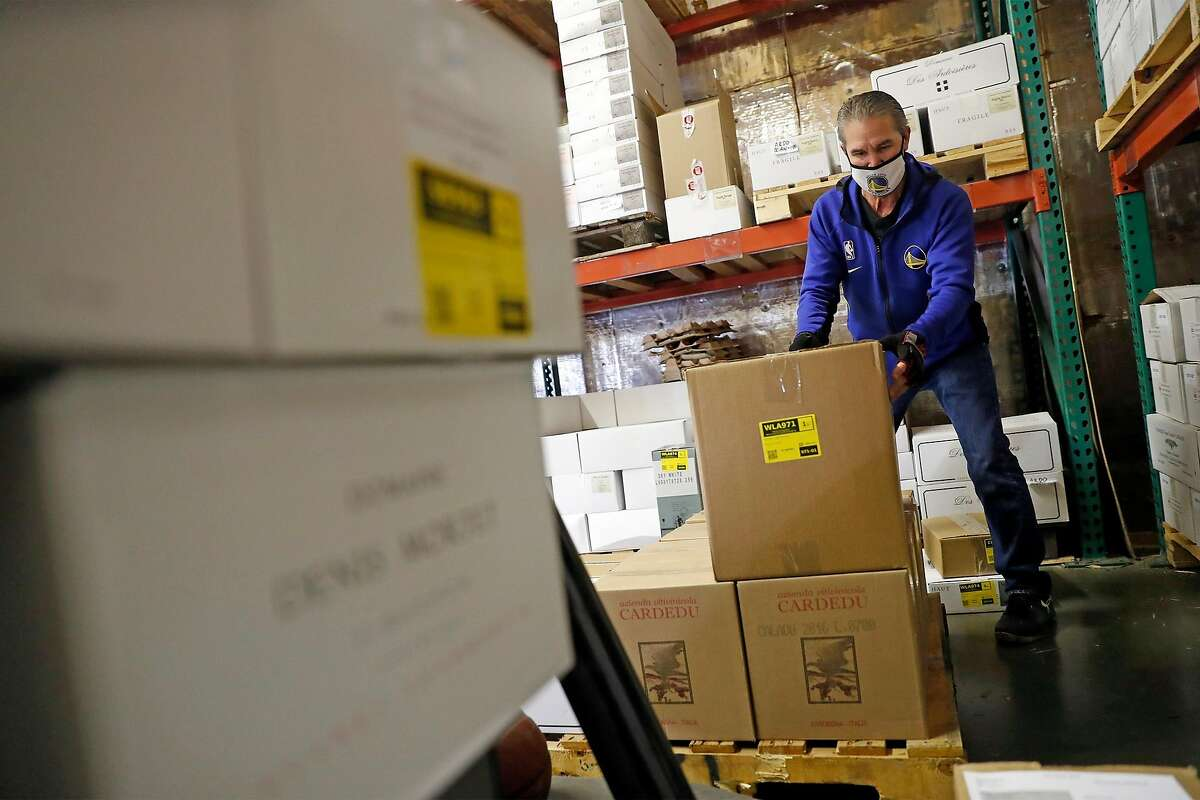 Chuck Gray loads cases of wine at the Martine's Wines warehouse in Novato. The importer will now be hit with a 25% tariff on all its French wines.