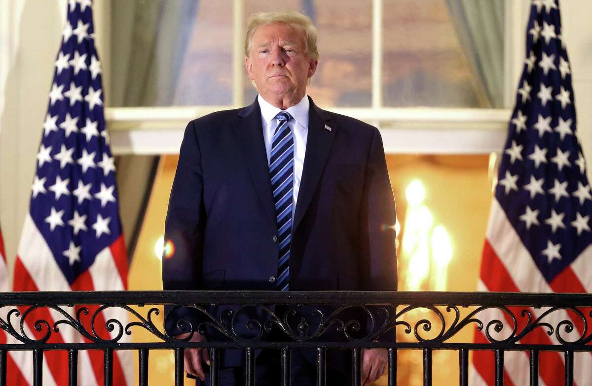 President Donald Trump stands on the Truman Balcony after returning to the White House.