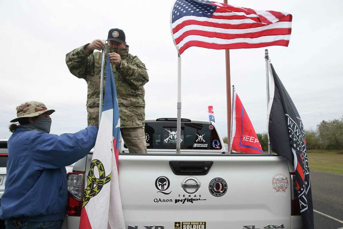 James Lambert, 56, place flags on his truck with the help of a friend at the Christian Fellowship Church in Harlingen, Texas, Tuesday. Supporters gathered for President Donald Trump's visit to the Rio Grande Valley and the border wall.