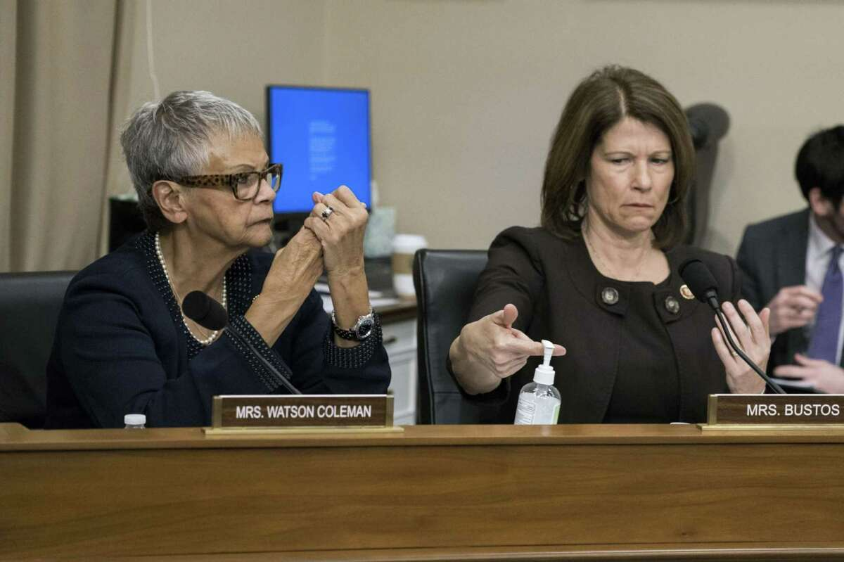 Rep. Bonnie Watson Coleman, D-N.J., left, and Rep. Cheri Bustos, D-Ill., use hand sanitizer during a hearing in Washington, D.C., on March 10, 2020. Watson Coleman, now hospitalized with the coronavirus, says she believes she was exposed after sheltering with several maskless colleagues during the Jan. 6, 2021, storming of the U.S. Capitol.