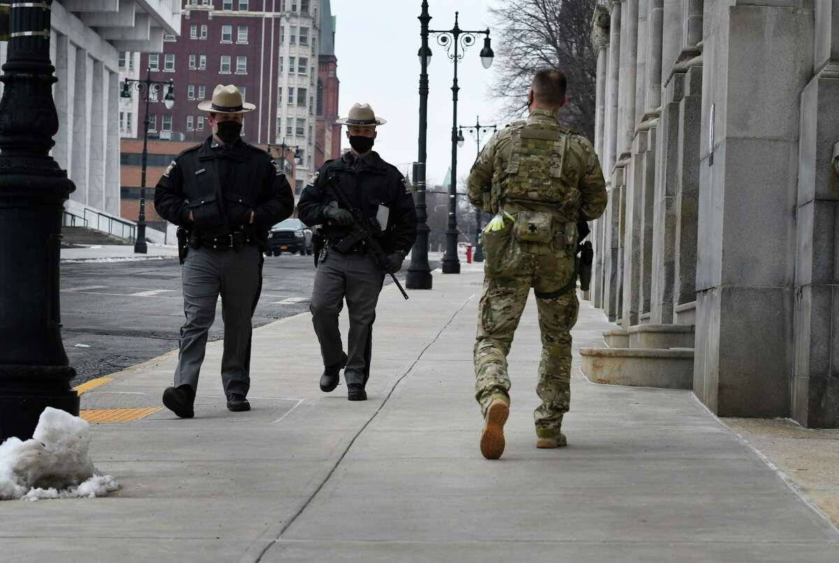New York State Troopers carrying assault rifles patrol the Capitol grounds as a safety precaution following the siege on the U.S. Capitol on Tuesday, Jan. 12, 2021, in Albany, N.Y. FBI says that protests are possible in all 50 state capitals leading up to Biden inauguration. (Will Waldron/Times Union)