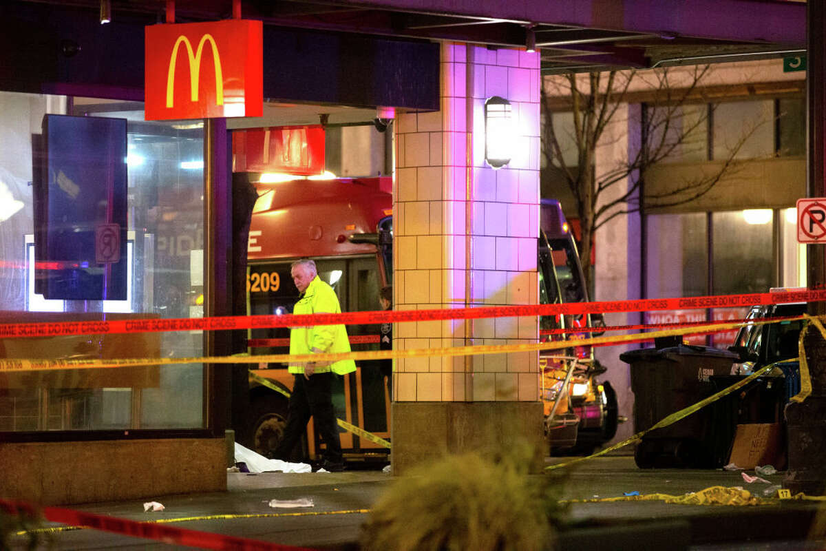 SEATTLE, WA - JANUARY 22: Police walk past the scene of a shooting at 3rd Avenue and Pine Streeton January 22, 2020 in the central business district of Seattle, Washington. Police say a woman was killed and seven people hurt, including a 9-year-old boy, by
