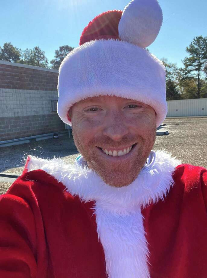 Jonathan Powell, Principal of Keefer Crossing Middle School in the New Caney Independent School District, spent a cold night on the roof of his school to raise funds for families in the district in need. To encourage donations, Powell dressed up as Santa Claus, the Grinch, and an elf. Photo: Provided