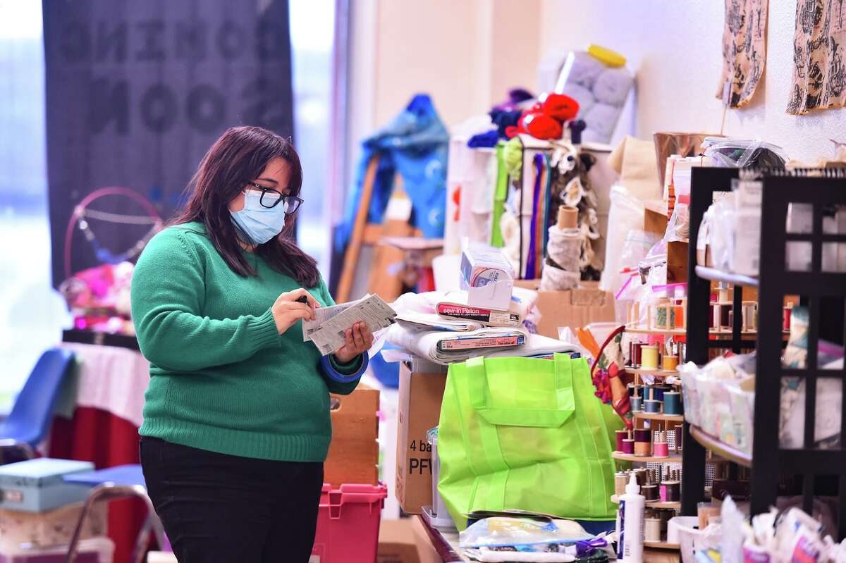 Mary Elizabeth Cantu, founder and executive director of Spare Parts, looks over donations of items that can be repurposed as art supplies. They are sold at the non-profit's new Center for Creative Reuse.