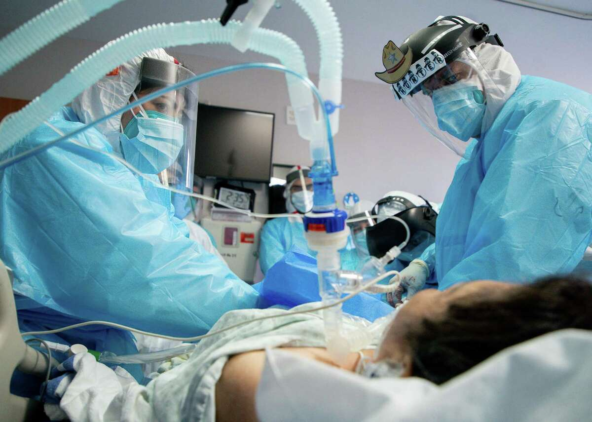 Dr. Joseph Varon, right, works to establish a venous line into a patient, inside the COVID-19 Intensive Care Unit on Thursday, Dec. 24, 2020, in Houston. The venous line was set up to start hypothermia therapy, which helps the patient maintain organ function.