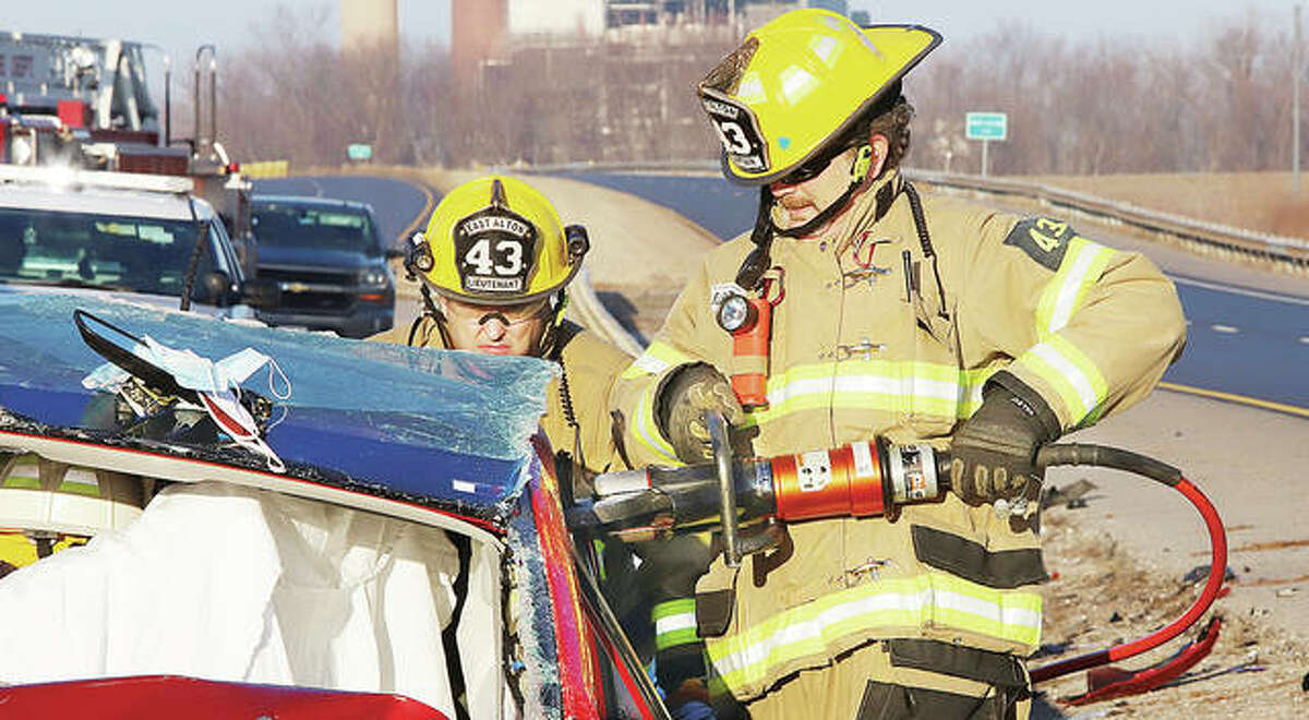 East Alton firefighters cut through the car's support posts to remove the top from the car Tuesday morning.