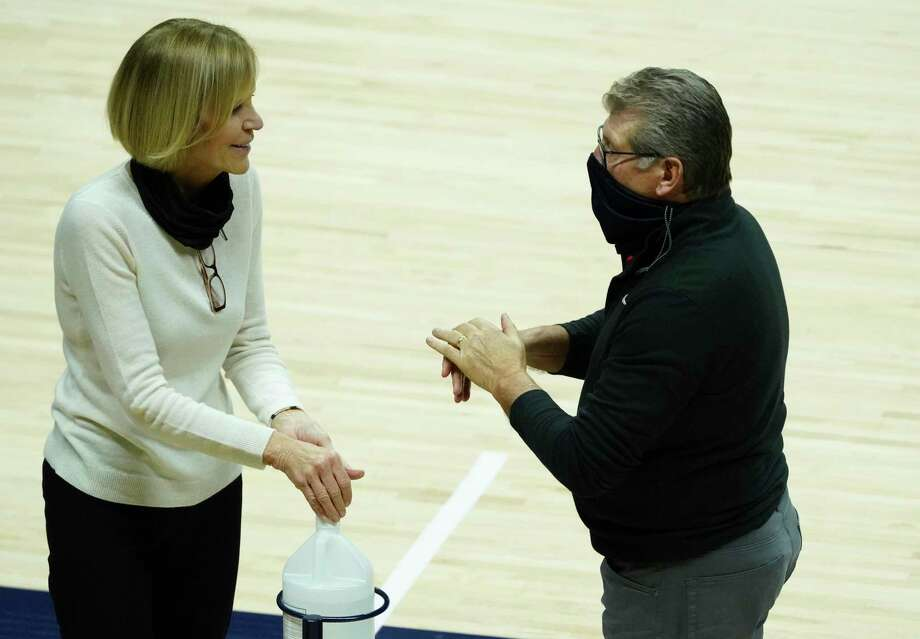 UConn associate head coach Chris Dailey, left, and coach Geno Auriemma sanitize their hands before Saturday's game against Providence in Storrs. Photo: David Butler II / Associated Press / David Butler II