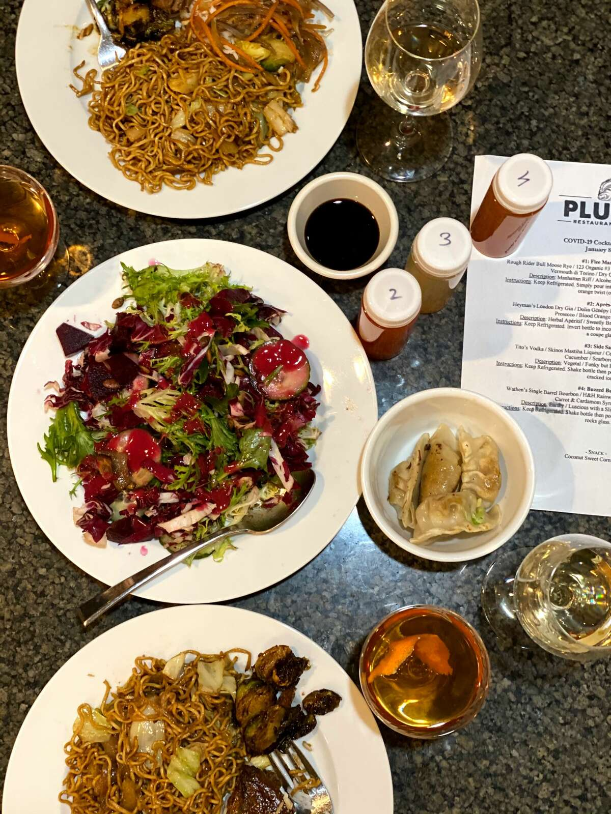 Susie Davidson Powell's multicourse takeout meal from dp: An American Brasserie included the restaurant's signature stir-fried noodles, called bakmi goreng (top and bottom plates), salad with roasted beets (middle) and, at center right, dumplings. (Photo by Susie Davidson Powell.)
