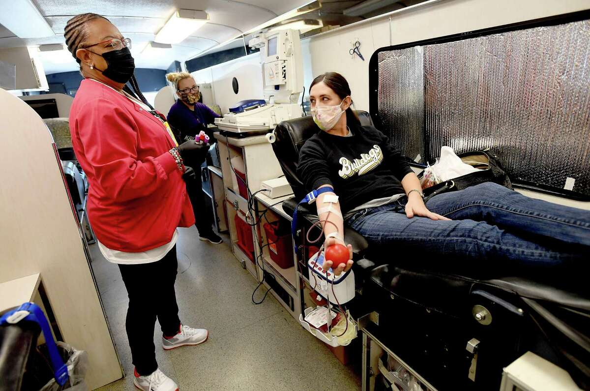 Lifeshare tech Denise Broussard talks with Emily Peters as she donates blood at the mobile Lifeshare bus in Nederland Friday. The Nederland Chamber of Commerce brought the unit down and took on advertising the stop in an effort to help the blood bank restock a low supply. Photo taken Friday, January 8, 2021 Kim Brent/The Enterprise