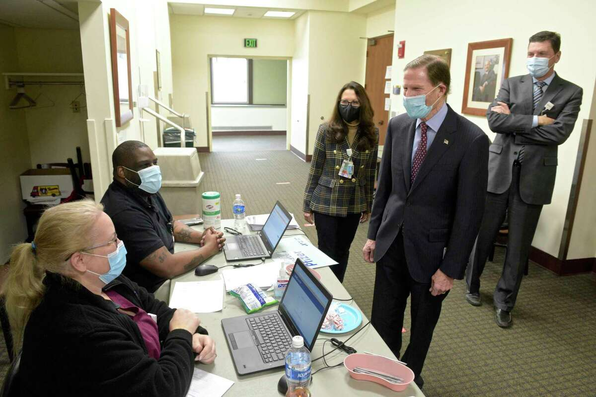 U.S. Senator Richard Blumenthal, talks with Tammy Perkins, a zone leader with housekeeping, left, and Jalel Bonnick, an IT special assistant, during a visit to Danbury Hospital on Tuesday afternoon. Blumenthal was there to view their COVID-19 vaccination station. Behind him are Sharon Adams, President of Danbury & New Milford Hospitals and John Murphy MD, CEO of Nuvance Health. January 12, 2021, in Danbury, Conn. Perkins and Bonnick were manning the registration table at the station.
