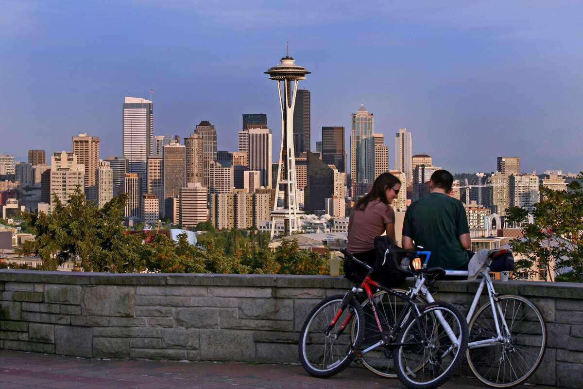 Two cyclists enjoy the view of downtown Seattle and the Space Needle.