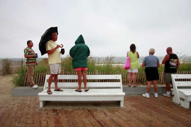 People including Ben Sharp, second from left, of Lewes, Del., watch weather from Hurricane Earl start to move into Rehoboth Beach, Del. on Friday, Sept. 3, 2010. (AP Photo/Jacquelyn Martin) Photo: Jacquelyn Martin, ASSOCIATED PRESS / Associated Press