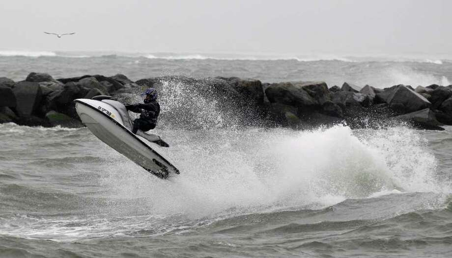 Joseph Mustafa of Fenwick Island, Del., rides a wave runner in the inlet in Ocean City, Md. as Hurricane Earl moves up the eastern coast, Friday, Sept. 3, 2010. (AP Photo/Rob Carr) Photo: Rob Carr, ASSOCIATED PRESS / Associated Press