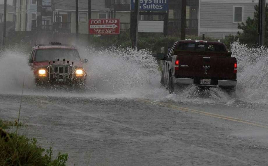 KILL DEVIL HILLS, NC - SEPTEMBER 03: Cars travel down a water covered beach road, on September 3, 2010 in Kill Devil Hills, North Carolina. Hurricane Earl was downgraded to a category 2 before brushing the Outer Banks early Friday morning causing minimal damage.  (Photo by Mark Wilson/Getty Images) Photo: Mark Wilson, Getty Images / 2010 Getty Images
