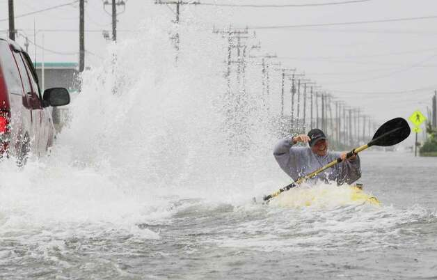 Kill Devil Hills, NC - SEPTEMBER 03:  Kellie Maier gets splashed by a passing car while kayaking on water covered Highway 12, on September 3, 2010 in Kill Devil Hills, North Carolina. Hurricane Earl was downgraded to a category 2 before brushing the Outer Banks early Friday morning causing minimal damage.  (Photo by Mark Wilson/Getty Images) Photo: Mark Wilson, Getty Images / 2010 Getty Images