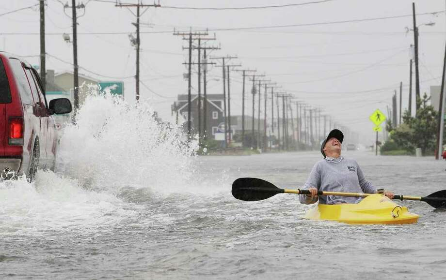 KILL DEVIL HILLS, NC - SEPTEMBER 03:  Kellie Maier laughs after getting splashed by a passing car while kayaking on water covered Hwy 12, on September 3, 2010 in Kill Devil Hills, North Carolina. Hurricane Earl was downgraded to a category 2 before brushing the Outer Banks early Friday morning causing minimal damage.  (Photo by Mark Wilson/Getty Images) Photo: Mark Wilson, Getty Images / 2010 Getty Images