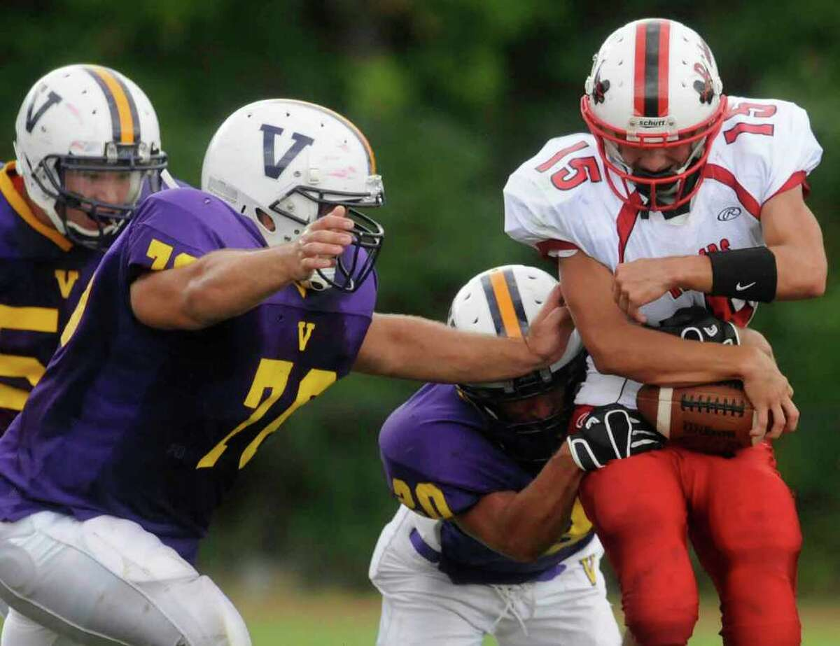 High school football -- Mechanicville's David Funaro keeps a precarious grip on the ball while running against Voorheesville. (Michael P. Farrell / Times Union )