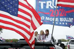 Supporters warm up in the bed of a truck as they meet at the Christian Fellowship Church in Harlingen, Texas for President Donald Trump's visit to the Rio Grande Valley and the border wall, Tuesday, Jan. 12, 2021.
