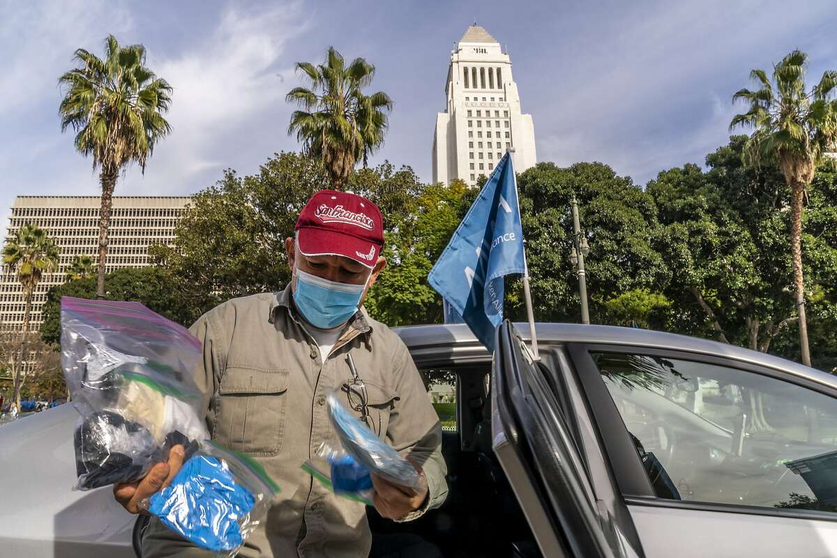 Uber driver Jose Luis Guevara, a member of the Mobile Workers Alliance, shows personal protective equipment, he provides to ride-sharing customers. Some drivers for app-based ride-hailing and delivery services are suing to overturn a California ballot initiative that makes them independent contractors instead of employees.