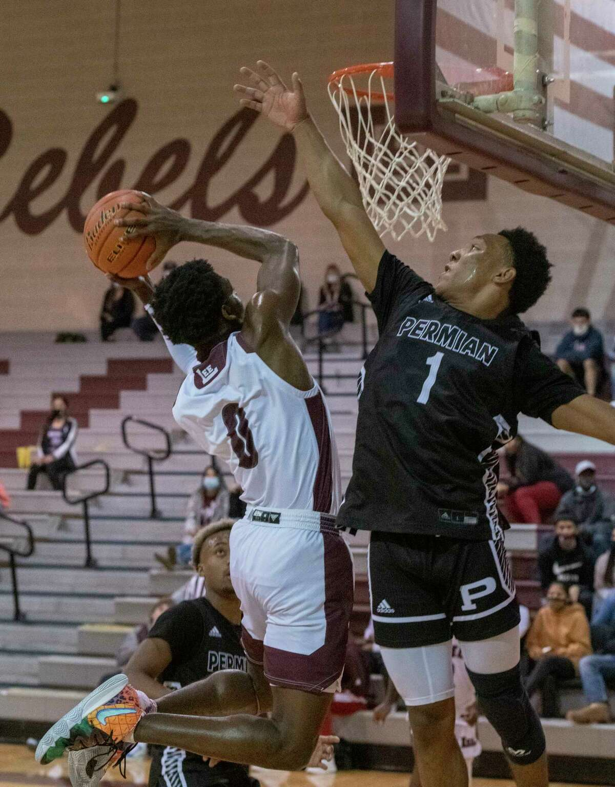 Lee High's Tre Hubert goes up for a shot as Permian's Cedric Baty tries to block 01/12/2021 at the Lee High gym. Tim Fischer/Reporter-Telegram